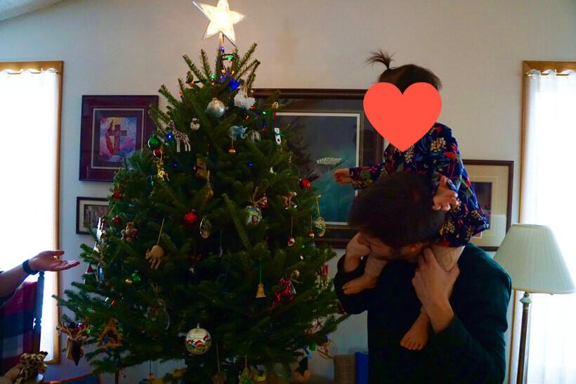 クリスマスの飾りつけをする夫と娘
